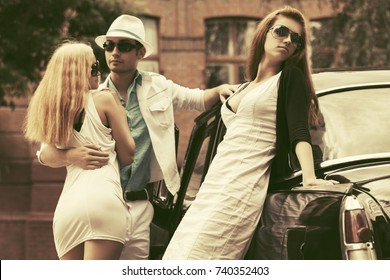 Young fashion man and women next to retro car in city street. Stylish male and female models outdoor