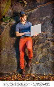 Young fashion man working on laptop computer, dressing in a gray shirt, red pants and brown boots, wearing a Fedora hat, sitting against rocks in a park.  Instagram Hefe Filter Effect.