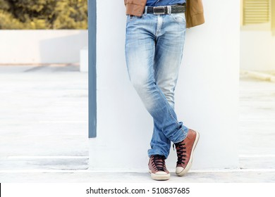 Young fashion man's with brown jacket and blue jeans.