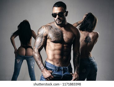 Young fashion man's legs in jeans. Sexy evening for young couple and sex protection. Muscular athletic sexy male, naked torso. Night party wiht young lovers. Stop sexual harassment. Safety sex concept