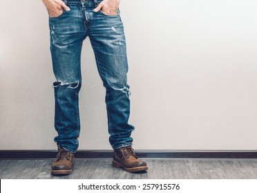 Young fashion man's legs in jeans and boots on wooden floor