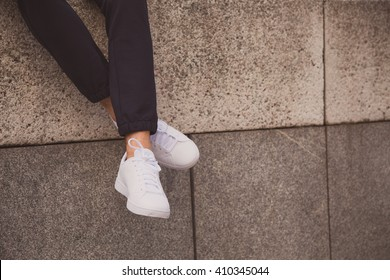 Young fashion man's legs with sneakers seated in stone wall. White shoes