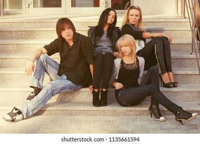 Young fashion men and women sitting on steps Stylish trendy male and female models