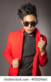 Young fashion middle eastern in red jacket with black fashion hairstyle posing in studio.