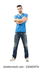 Young fashion model with arms wrapped around himself looking at camera. Full body length isolated over white background.