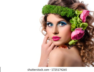 A young fashion model with bright makeup and flowers in her hair. Blue eye shadow and red lipstick. Close-up studio portrait