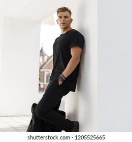 Young fashion model man with bag in black shirt and pants with black bag stands near white wall