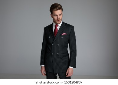 young fashion model wearing double breasted suit, looking to side, standing on grey background