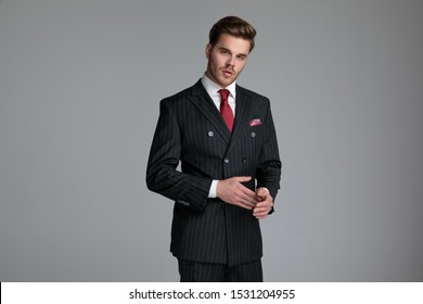 young fashion model wearing double breasted suit, touching palms with fingers, standing on grey background