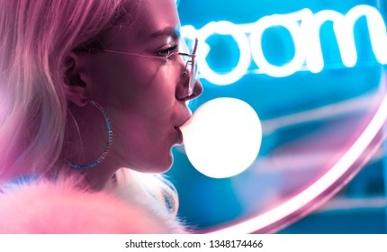 Young fashion teen girl in fur glasses blowing bubble gum illuminated with street neon blue pink sign, beautiful millennial woman in trendy night light glow back to 80s concept, profile close up view