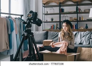 young fashion vlogger sitting in front of camera with shirt