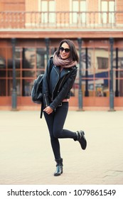 Young fashion woman with backpack walking in city street Stylish female model in black jeans and leather jacket outdoor