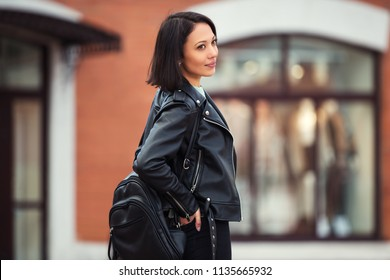 Young fashion woman with backpack walking in city street Stylish female model wearing black leather jacket outdoor