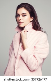 young fashion woman beauty portrait posing in studio wearing in pink coat