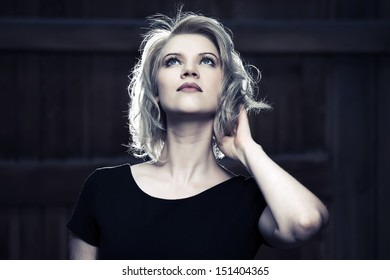 Young fashion woman in black dress looking up walking on street