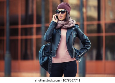Young fashion woman in black leather jacket using cell phone in city street Stylish female model wearing sunglasses beanie and knitted scarf outdoor