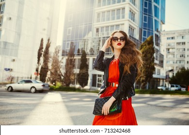 Young fashion woman in casual red dress and black leather jacket over urban city background autumn portrait. Hipster girl posing at street. Fashionable long hair model in elegant autumn clothes.