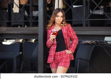 Young fashion woman with glass of wine at sidewalk cafe  Stylish female model in red tweed jacket and shorts suit