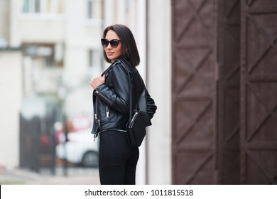 Young fashion woman with handbag walking in city street Stylish female model in sunglasses and black leather jacket outdoor