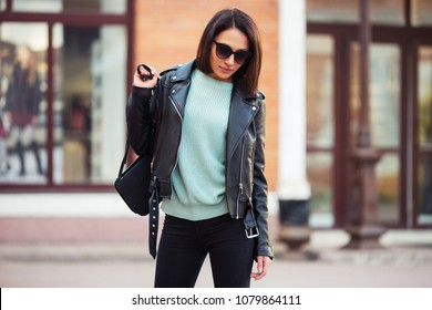 Young fashion woman with handbag walking in city street Stylish female model in black jeans and leather jacket outdoor
