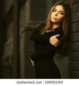 Young fashion woman leaning on brick wall on city street Stylish female model with long brown straight hairs wearing black dress