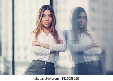 Young fashion woman leaning on mall window Stylish female model in white shirt and gray mini skirt
