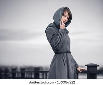 Junge Modefrau auf Geländer Stilvolles Frauenmodell in grauem klassischem Mantel und Kopfschal