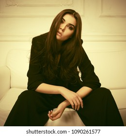 Young fashion woman with long brown hairs sitting on sofa at home Stylish female model in black suit jacket and pants