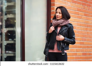 Young fashion woman looking at window display Stylish female model wearing black leather jacket and knit scarf