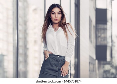 Young fashion woman next to mall window on city street Stylish female model in white shirt and gray skirt