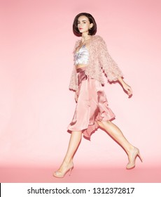 young fashion woman in pink clothes run on pink background, full lenght