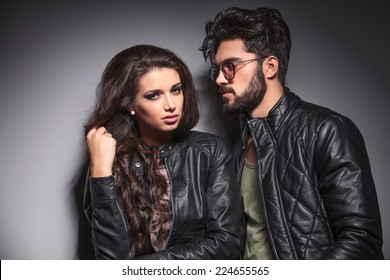 Young fashion woman pulling her hair while her lover is looking at her. Against a grey wall.