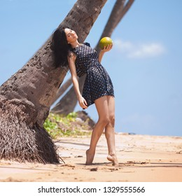 Young fashion woman relax on the beach. Happy island lifestyle. Prety woman hold coconut under palm tree on the tropical beach. Ocean beach relax, travel, vacation concept