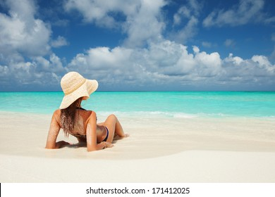 Young fashion woman relax on the beach of sea. Happy island lifestyle. Vacation at Paradise. Happy woman enjoy crystal-blue water of tropical sea. Ocean beach relax, travel vacation
