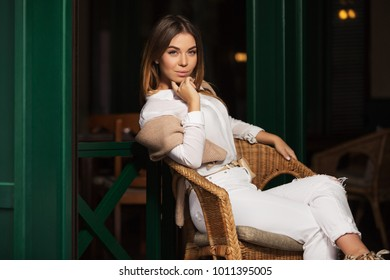 Young fashion woman sitting on wicker chair at sidewalk cafe. Stylish female model in white blouse and ripped jeans