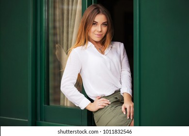 Young fashion woman sitting on window in sidewalk cafe. Stylish female model with straight hairs in white blouse
