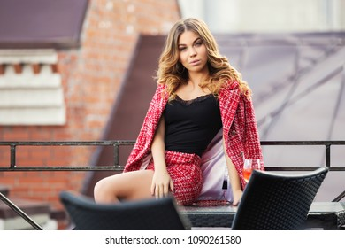 Young fashion woman sitting on table at sidewalk cafe Stylish female model in red tweed jacket and skirt suit