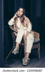 Young fashion woman sitting on wicker chair at sidewalk cafe. Stylish female model in white shirt and ripped jeans