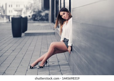 Young fashion woman sitting on the mall window  Stylish female model in white shirt and gray mini skirt