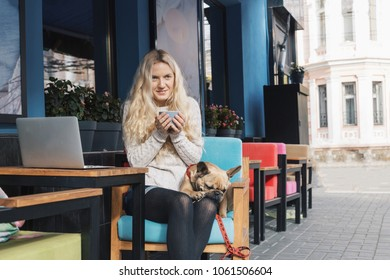 Young fashion woman sitting at the table withe her french bulldog and drinking coffee in cafe. Stylish female model with blonde hairs