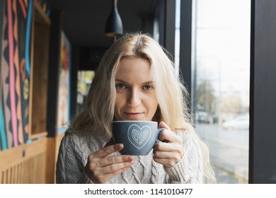 Young fashion woman sitting at the table and drinking coffee in cafe. Stylish female model with blonde hairs