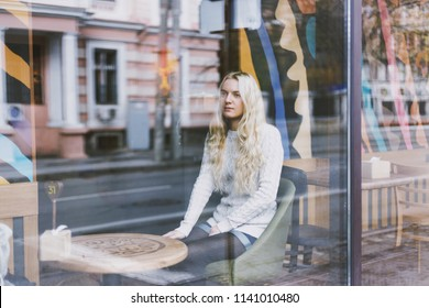 Young fashion woman sitting at the table in cafe. Stylish female model with blonde hairs