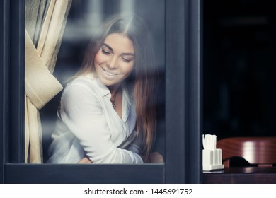 Young fashion woman sitting at the table in cafe Stylish female model with straight hairs in white shirt