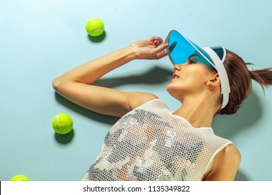 young fashion woman smiling and looking left side near tennis ball on blue background