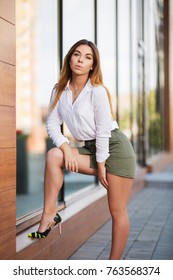 Young fashion woman standing next to mall window in a city street. Stylish female model in white blouse and short skirt outdoor