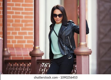 Young fashion woman in sunglasses leaning on railing in city street Stylish female model in black leather jacket outdoor