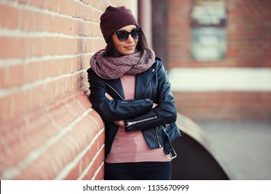 Young fashion woman in sunglasses leaning on brick wall Stylish female model wearing black leather jacket and knitted scarf