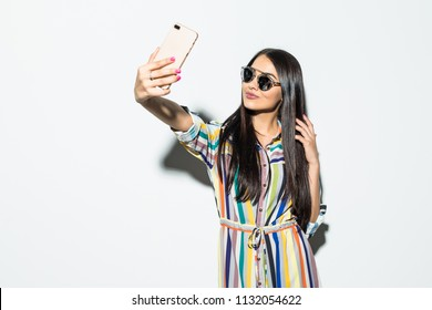 Young fashion woman take selfie from hands phone on gray background