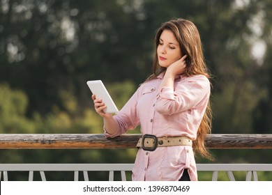Young fashion woman using digital tablet computer outdoor Stylish female model with long brown hairs in pale pink shirt