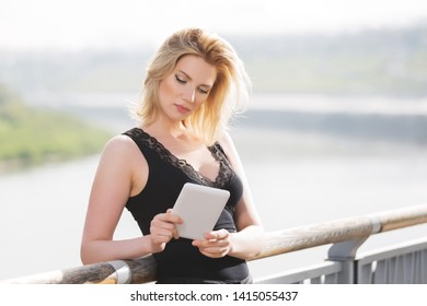 Young fashion woman using digital tablet computer outdoor  Stylish female model with blonde hairs in black tank top